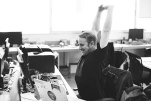 black and white image of man stretching at his desk