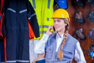 woman in grey vest with yellow hard hat inside room